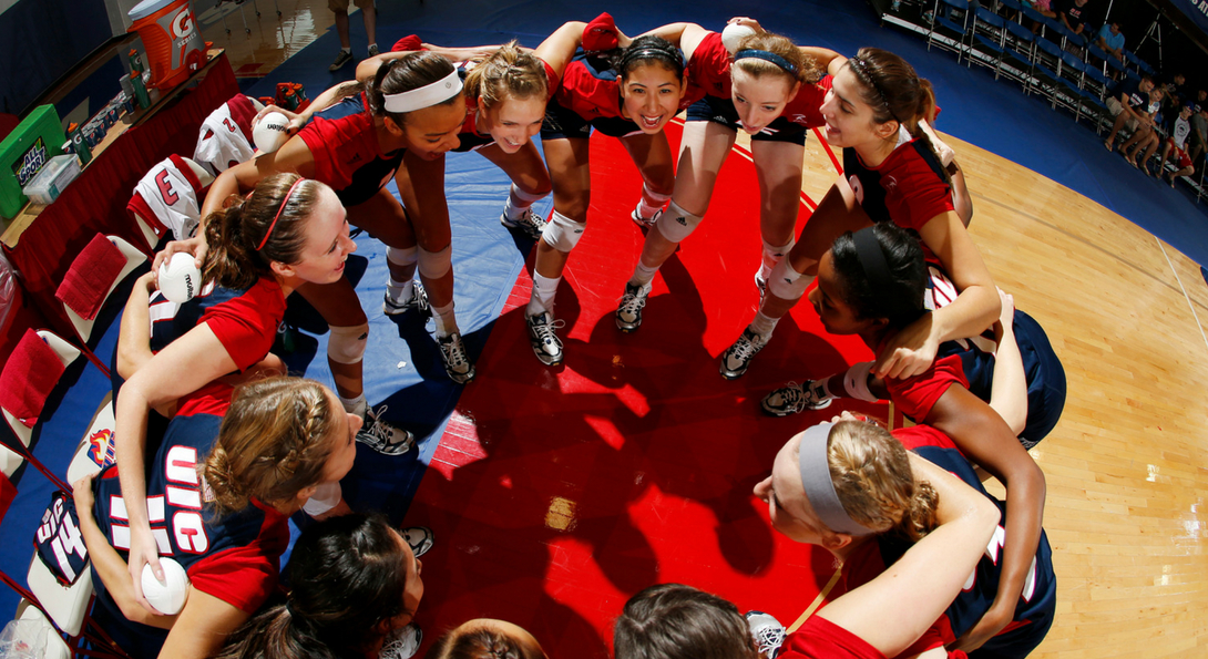 female volleyball players huddle in a circle before a game