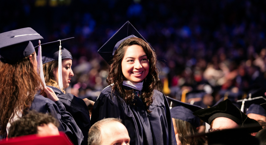 female student in cap and gown at commencement ceremony