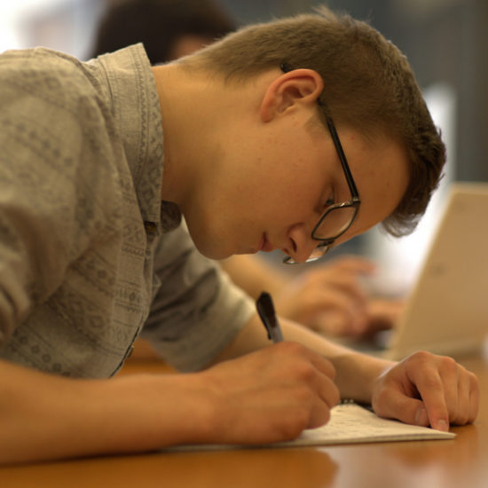 male student writing in a notebook