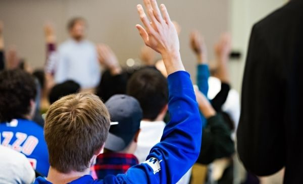 view of the back of a student in a blue shirt raising his hand in class